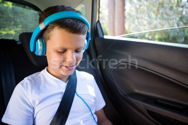 Teenage boy with headphones sitting in the back seat of car Stock photo © wavebreak_media