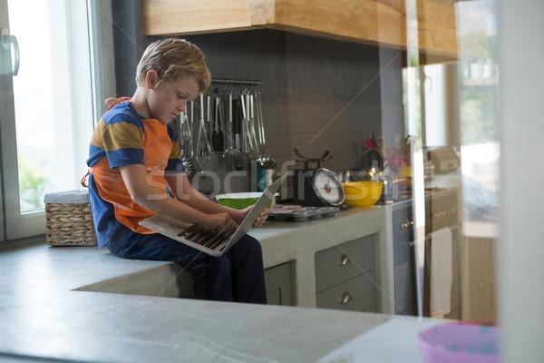 Fiú laptopot használ ül konyhapult megnyugtató pult Stock fotó © wavebreak_media