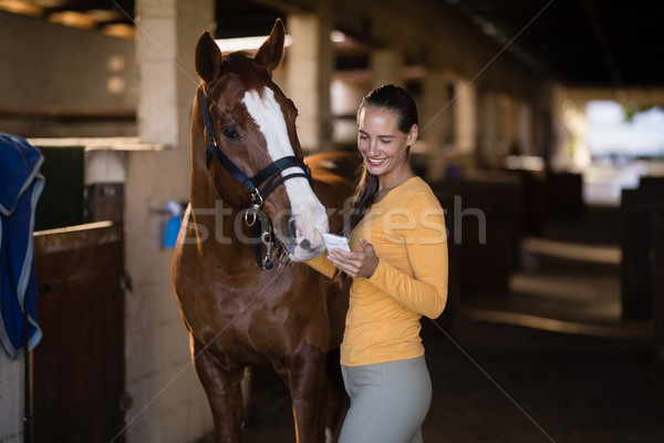 女性 ジョッキー スマートフォン 立って 馬 安定した ストックフォト © wavebreak_media