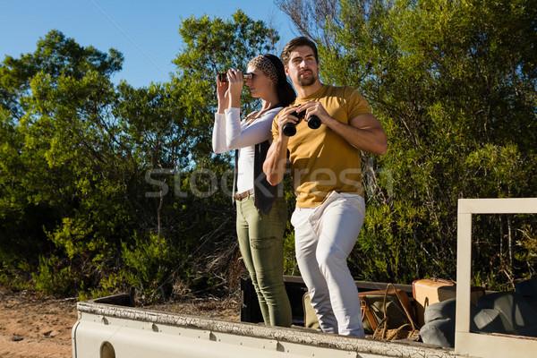 Couple looking through binoculars in off road vehicle Stock photo © wavebreak_media