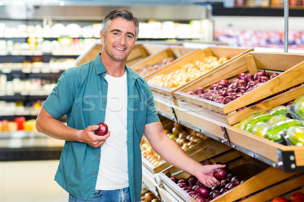 Smiling man choosing a onion Stock photo © wavebreak_media