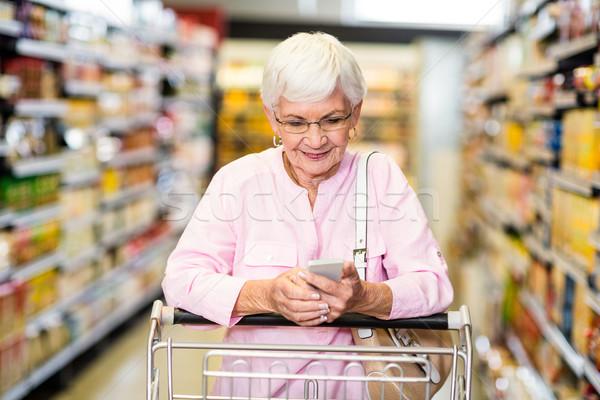 Senior mulher telefone empurrando carrinho supermercado Foto stock © wavebreak_media