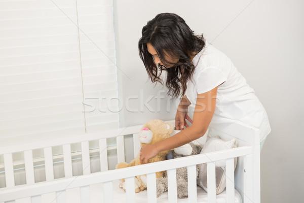 Smiling brunette putting in order the crib Stock photo © wavebreak_media