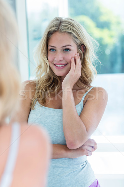 Smiling beautiful young woman looking at herself in the bathroom Stock photo © wavebreak_media