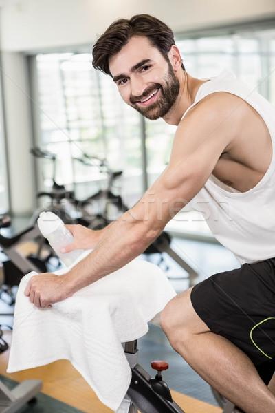 Smiling man on exercise bike looking at the camera Stock photo © wavebreak_media