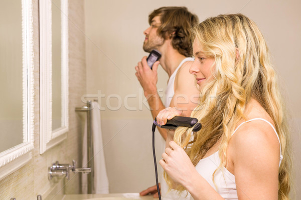 Cute couple using a razor and a straightener Stock photo © wavebreak_media