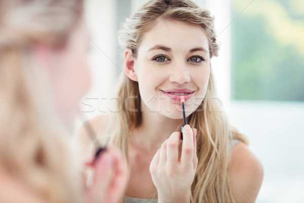 Portrait of smiling young woman applying lip gloss Stock photo © wavebreak_media