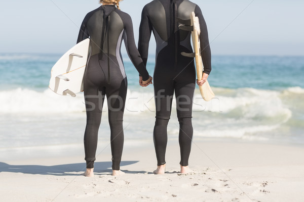 Rear view of couple with surfboard holding hands on the beach Stock photo © wavebreak_media