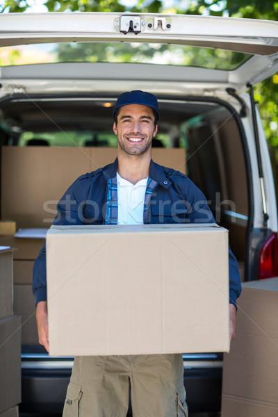 Portrait of smart delivery man carrying cardboard box Stock photo © wavebreak_media