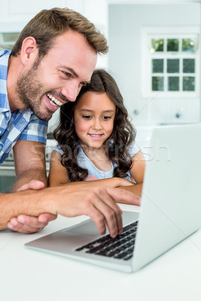 Man with daughter using laptop computer at home Stock photo © wavebreak_media