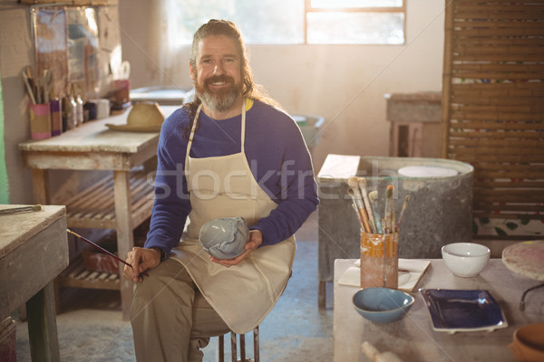 Smiling male potter painting on bowl Stock photo © wavebreak_media