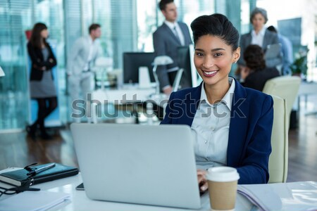 Businesswoman standing in office corridor with coffee cup Stock photo © wavebreak_media