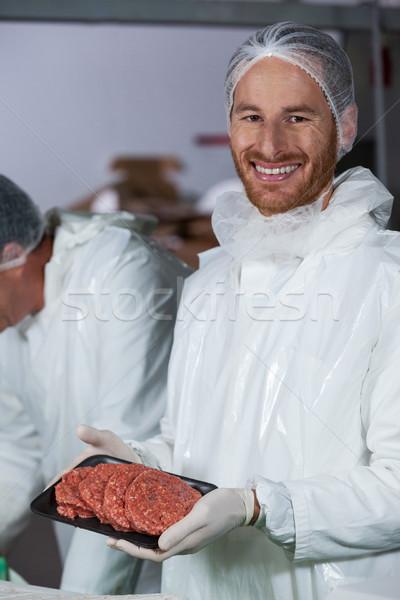 Butcher holding raw meat patties arranged in tray Stock photo © wavebreak_media