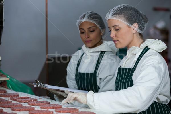 Female butchers maintaining records on clipboard Stock photo © wavebreak_media