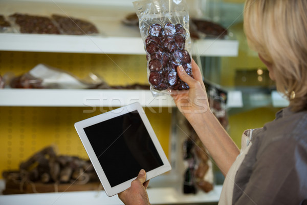 Female staff maintain records of meat on digital tablet at counter Stock photo © wavebreak_media