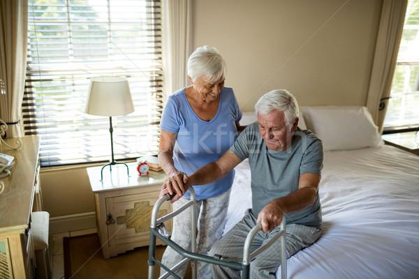 Senior woman helping man to walk with a walker Stock photo © wavebreak_media