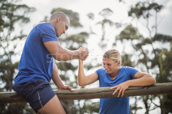 Man assisting woman to climb a hurdles during obstacle training Stock photo © wavebreak_media