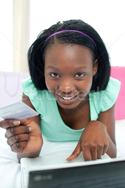 Cheerful woman shopping on-line lying on her bed Stock photo © wavebreak_media