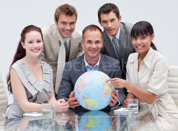 Smiling business team holding a terrestrial globe Stock photo © wavebreak_media