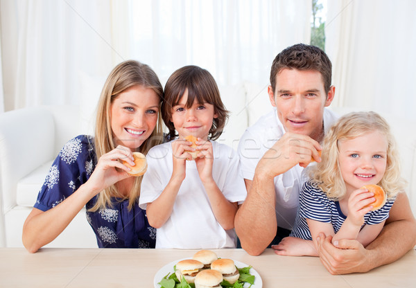 Smiling family eating burgers in the living room Stock photo © wavebreak_media