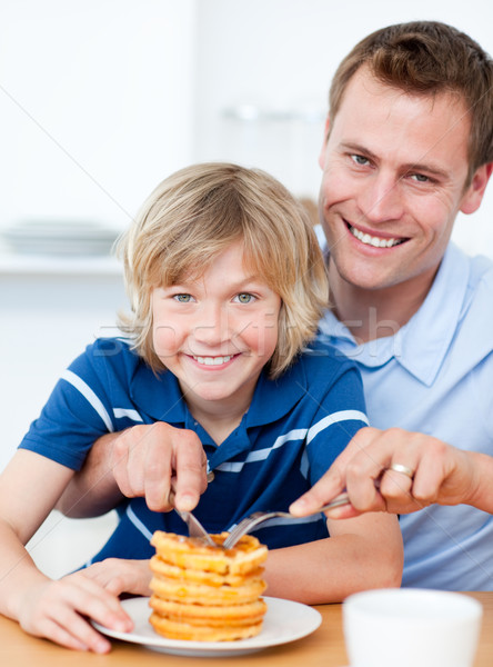 Smiling father and his son eating waffles Stock photo © wavebreak_media