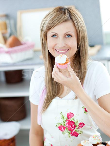 Encantado mulher alimentação pequeno bolo cozinha Foto stock © wavebreak_media