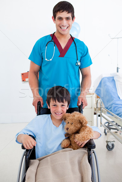 Stock photo: Portrait of a cute little boy sitting on wheelchair and a doctor at the hospital