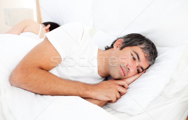 Upset man lying in his bed separately from his wife Stock photo © wavebreak_media