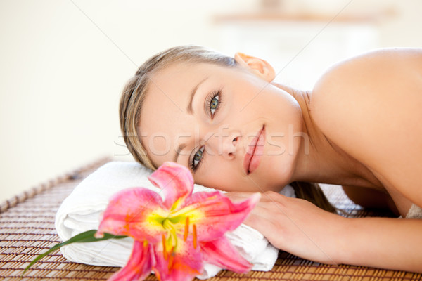 Close-up of a delighted woman lying on a massage table with a flower Stock photo © wavebreak_media