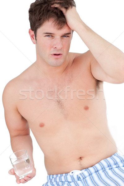 tired man in pyjamas having a headache holding a glass of water against a white background Stock photo © wavebreak_media