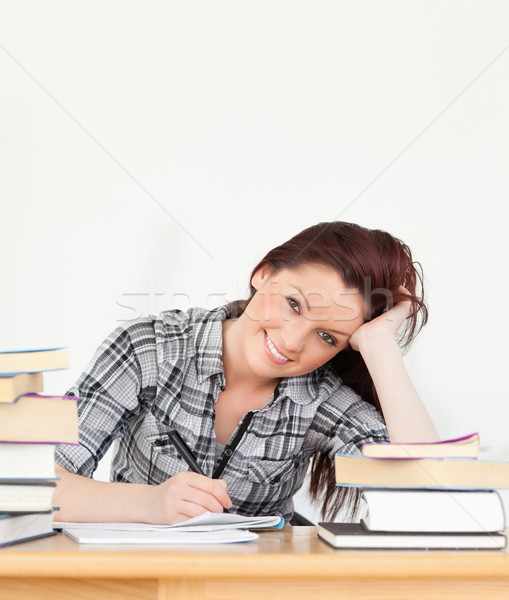 Attractive joyful red-haired girl studying for an examination at her desk Stock photo © wavebreak_media