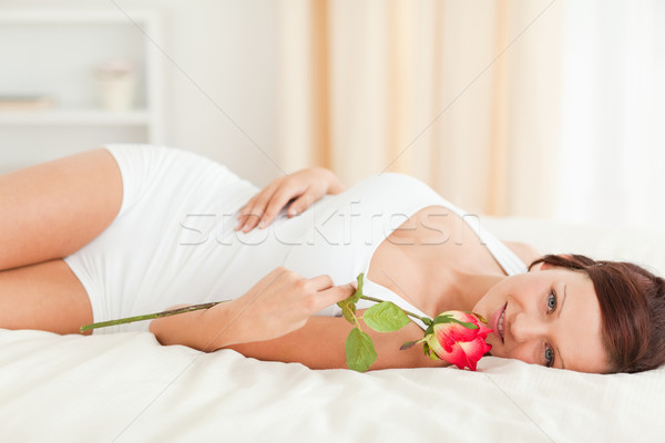 Young Woman with a rose looking into camera in her bedroom Stock photo © wavebreak_media