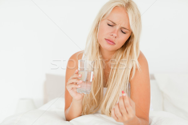 Woman taking a pill in her bedroom Stock photo © wavebreak_media