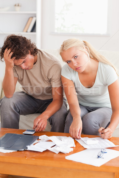 Despaired worn out couple calculating their expenses in the living room Stock photo © wavebreak_media
