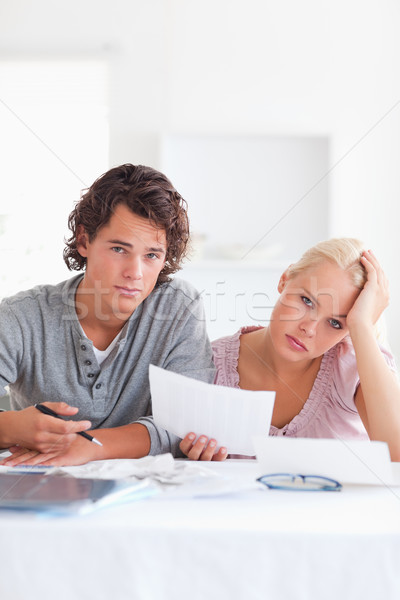 Unhappy couple reading a letter in the living room Stock photo © wavebreak_media