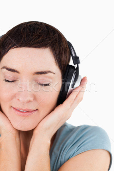 Portrait of a delighted woman enjoying some music against a white background Stock photo © wavebreak_media