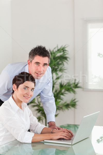 Portrait of a manager and his secretary posing with a laptop in an office Stock photo © wavebreak_media