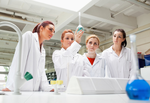 Science students looking at a liquid in a flask in a laboratory Stock photo © wavebreak_media