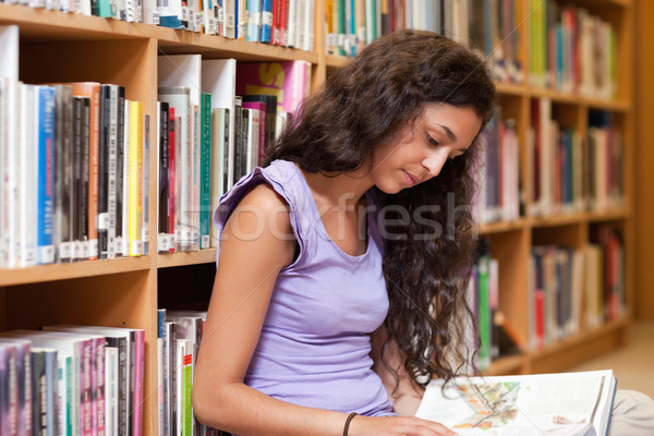 Young student reading a book in a library Stock photo © wavebreak_media