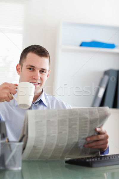 Smiling young businessman reading the newspaper and having a coffee Stock photo © wavebreak_media