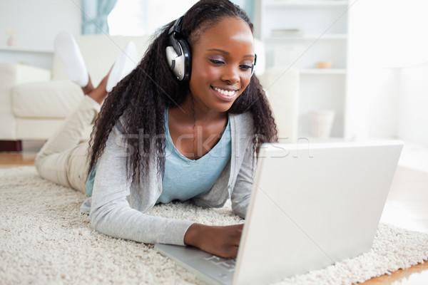 笑顔の女性 階 ノートブック 音楽を聴く 笑顔 ホーム ストックフォト © wavebreak_media