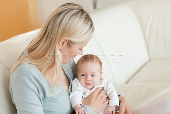 Young mother on the sofa with her newborn on her lap Stock photo © wavebreak_media