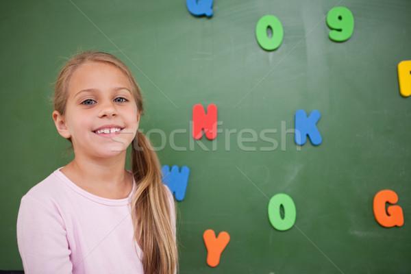 Jóvenes colegiala posando pizarra aula sonrisa Foto stock © wavebreak_media