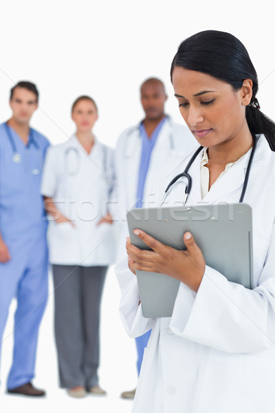 Female doctor reading notes with staff members behind her against a white background Stock photo © wavebreak_media