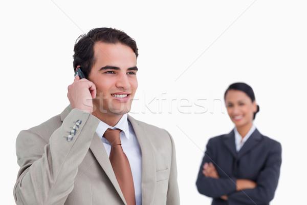 Sorridente vendedor telefone móvel colega atrás branco Foto stock © wavebreak_media