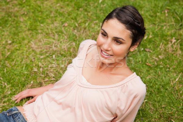 Uśmiechnięta kobieta patrząc prosto przed leży w dół Zdjęcia stock © wavebreak_media