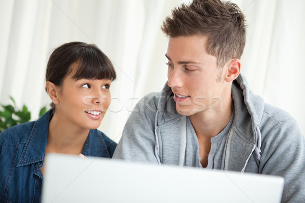 Students with conspiratorial look using a laptop Stock photo © wavebreak_media
