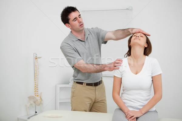 Serious practitioner placing his hand on the forehead of a woman in an office Stock photo © wavebreak_media