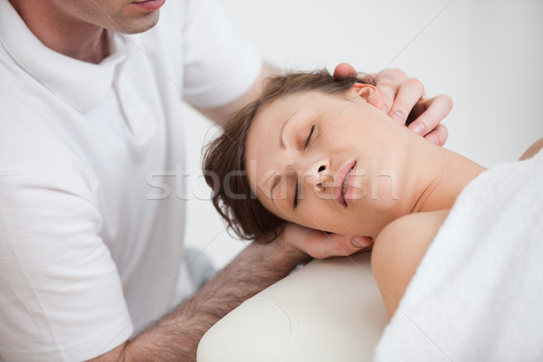 Woman being massaging by the doctor while having the head turn in the side inddor Stock photo © wavebreak_media
