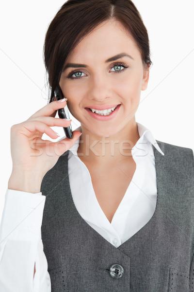 Blue eyed brunette in suit on the phone against white background Stock photo © wavebreak_media
